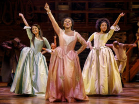 3 ladies in early 1700 dresses, snap their fingers in the air. They are the Schuyler sisters looking for a mind at work.